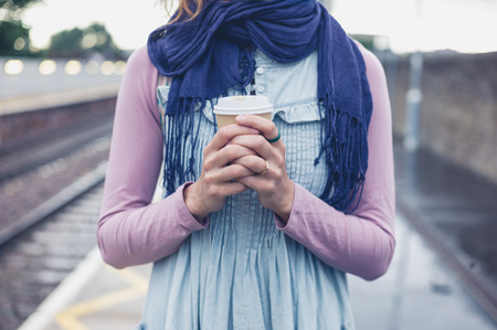 women holding cup: A young woman is standing on a platform with a cup of coffee and is waiting for the train Stock Photo