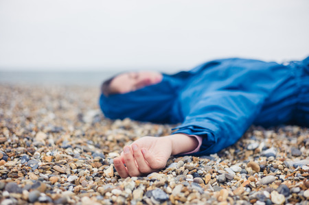 fainted: An unconscious woman is lying on a shingle beach
