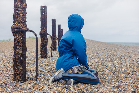 rusty fence: A young woman is sitting on the shingle by a rusty fence on the beach Stock Photo