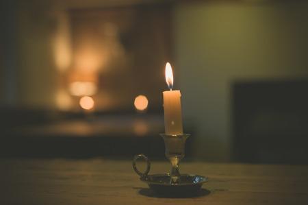 Een brandende kaars op een tafel in een eetzaal