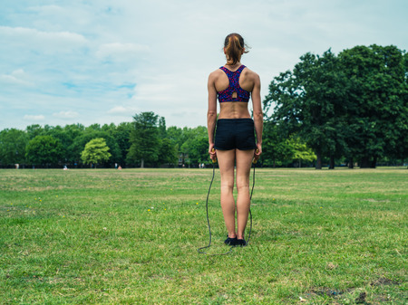 jump rope: A fit and athletic young woman is standing on the grass in a park and is exercising with a jump rope