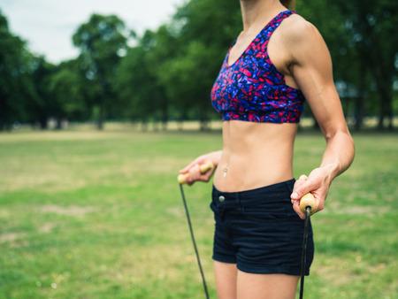 saltar la cuerda: Una joven mujer en forma y atlético está de pie en la hierba en un parque con una cuerda de saltar