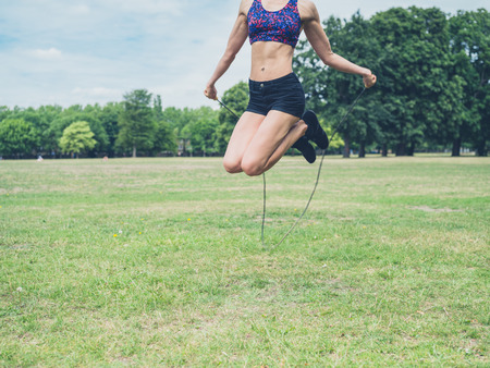 jump rope: A fit and athletic young woman is skipping with a jump rope in the park on a summer day