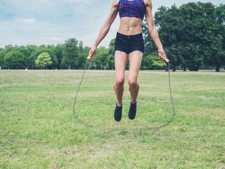 saltar la cuerda: Una joven mujer en forma y atl�tico est� saltando con una cuerda para saltar en el parque en un d�a de verano Foto de archivo