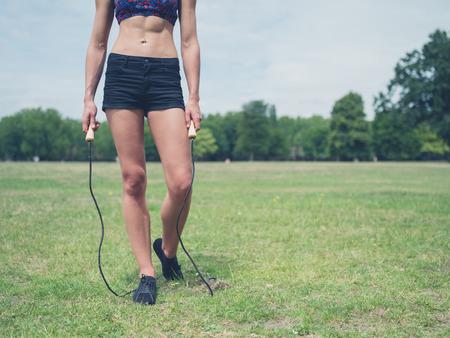 saltar la cuerda: Una joven mujer en forma y atractiva est� de pie en la hierba en un parque con una cuerda de saltar en un d�a soleado de verano