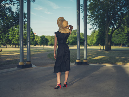 bandstand: An elegant young woman wearing a hat and a dress is standing in a bandstand in a park at sunset