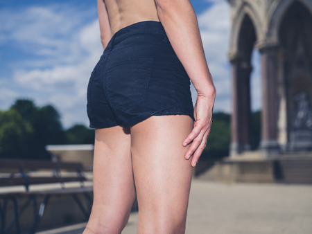 bum: Rear view shot of a fitness womans bum and lower body as she is standing in a park on a sunny summer day