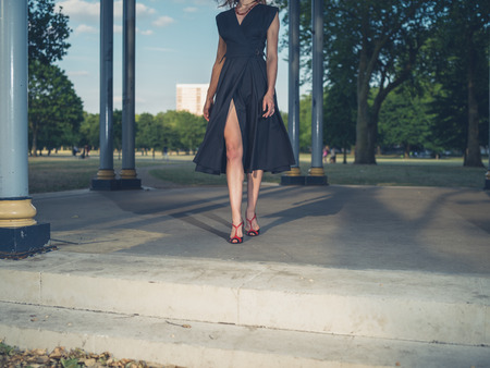 bandstand: An elegant woman wearing a dress is standing in a bandstand in a park at sunset Stock Photo