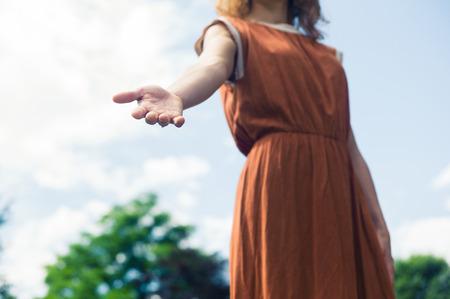 Una mujer joven está de pie al aire libre en la naturaleza en un día soleado y está ofreciendo una mano amiga Foto de archivo - 42882972
