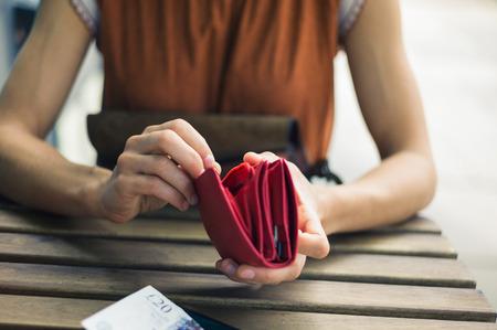 factura: Una mujer joven está sentado fuera y está abriendo su bolso para conseguir algo de dinero para el pago de la factura en un café