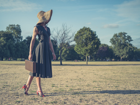 Vintage filtered shot of an elegant young woman in high heels and a dress walking in the park with a briefcase Stock Photo