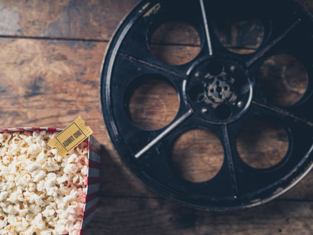 blue film: Cinema concept with vintage film reel, popcorn and a movie ticket