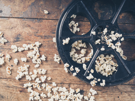 retro cinema: Cinema concept of vintage film reel with popcorn on wooden surface