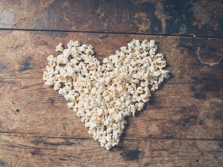 movie popcorn: Cinema concept of popcorn arranged in a heart shape on wooden table Stock Photo