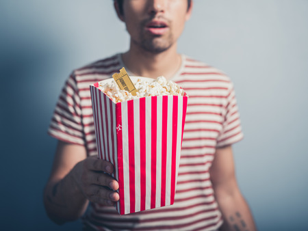 movie ticket: A young man is holding a box of popcorn with a cinema ticket in it