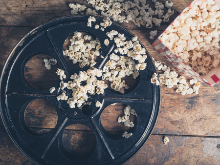 retro cinema: Cinema concept of vintage film reel with popcorn on wooden surface