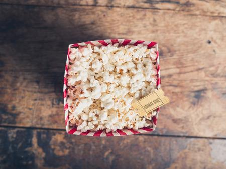 palomitas: Cine concepto de billete de palomitas y de la película en una mesa de madera
