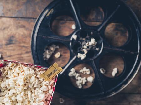 movie film reel: Cinema concept with vintage film reel, popcorn and a movie ticket