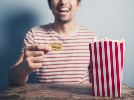 movie ticket: A happy young man is sitting at a table with a box of popcorn and a movie ticket in his hand