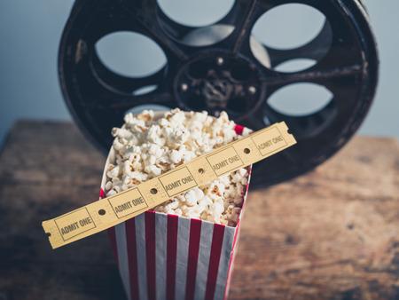 palomitas: Cine concepto de rollo de película antigua con los boletos de las palomitas y de la película en una superficie de madera Foto de archivo