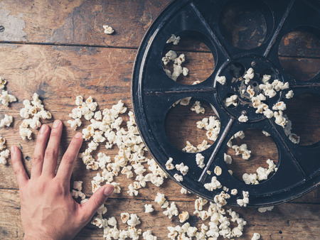 Movie theater: Cinema concept of hand with vintage film reel and popcorn