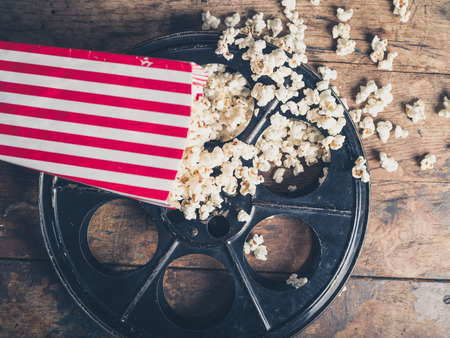 Cinema concept of vintage film reel with popcorn on wooden surface