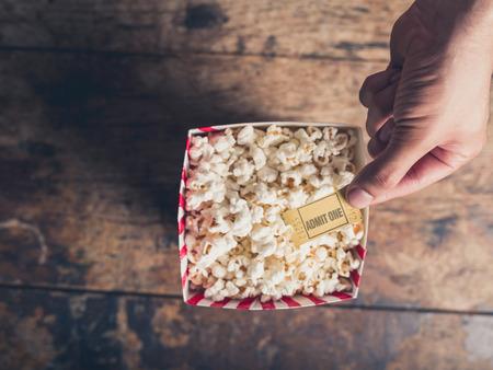 palomitas de maiz: Cine concepto de billete de retenci�n pel�cula mano por encima de una caja de palomitas de ma�z Foto de archivo