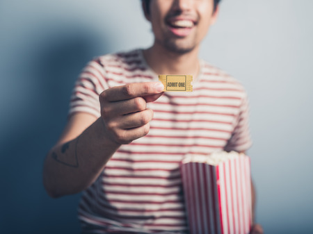 film: A happy young man with a box of popcorn is holding a cinema ticket Stock Photo