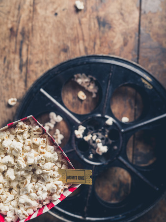 cinema ticket: Cinema concept with vintage film reel, popcorn and a movie ticket