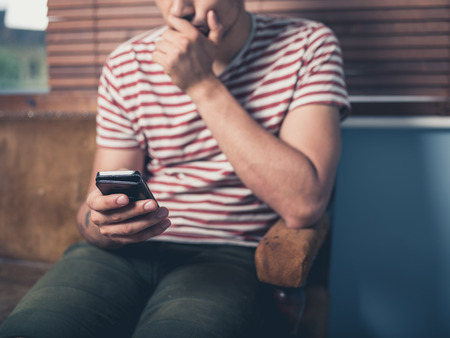 sad people: A young man is sitting on a sofa and is using a smart phone at home Stock Photo
