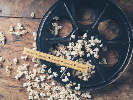 movie reel: Cinema concept of vintage film reel with popcorn and movie tickets