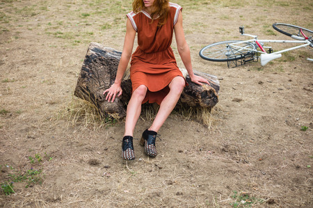 bruised: A young woman with bruises on her leg is sitting on a log outside, there is a bicycle in the background Stock Photo