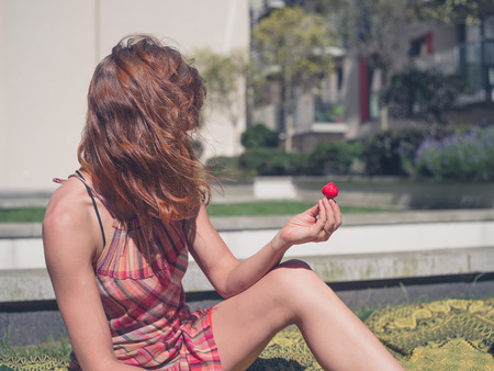 apartment block: A young woman is sitting on the grass outside an apartment block with a strawberry in her hand