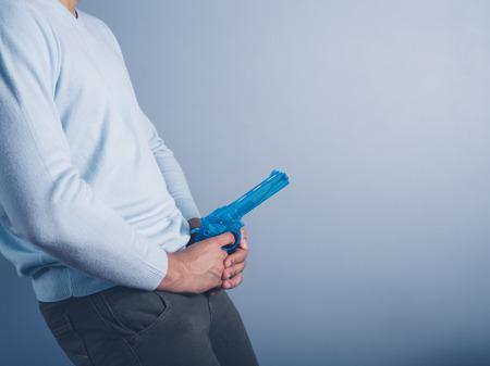 若い男は水鉄砲と彼の股間の前にそれを保持しています。