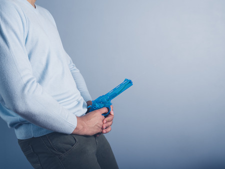 crotch: A young man is posing with a water pistol and is holding it in front of his crotch