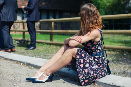 smartly: A young woman wearing a dress is sitting outside on a farm with smartly dressed people participating in a social event or gathering