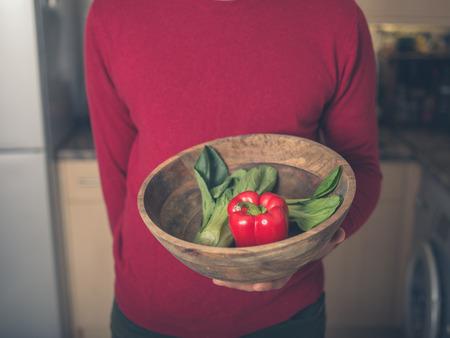 Een jonge man is permanent in een keuken met een kom van paksoi en rode peper