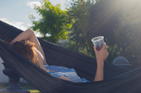 hammock: Una mujer joven con una bebida en la mano es relajante en una hamaca al aire libre en un jard�n en un d�a soleado de verano Foto de archivo
