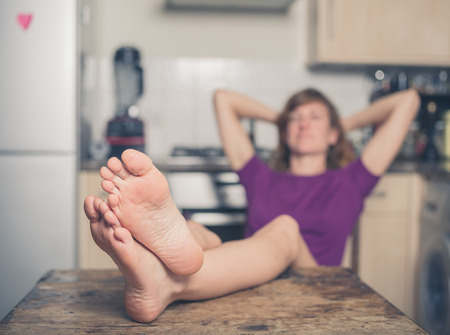 feet on desk: A young woman is relaxing in a kitchen with her bare feet on a table Stock Photo