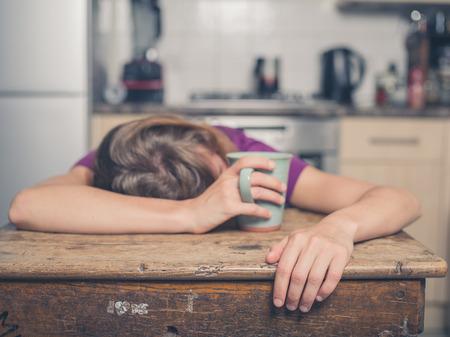 cabeza: Una joven mujer cansada está teniendo una taza de té y está descansando la cabeza sobre una mesa