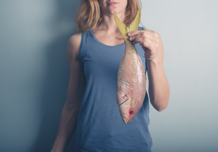 carribean: A young woman is holding an exotic Carribean snapper Stock Photo