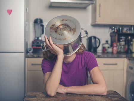 懸念している若い女性は彼女の頭の上に鍋で台所でテーブルに座ってください。