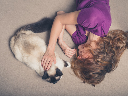 petting: Overhead shot of a young woman lying on a carpet at home and petting a cat