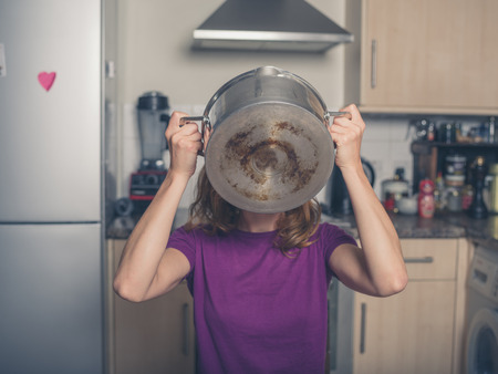 slurp: A young woman is drinking from a pot in a kitchen