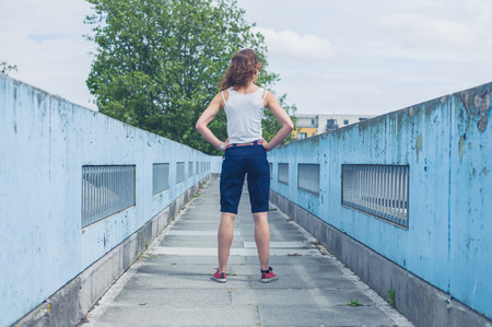 foot bridges: A stylish young woman is standing on a footbridge Stock Photo