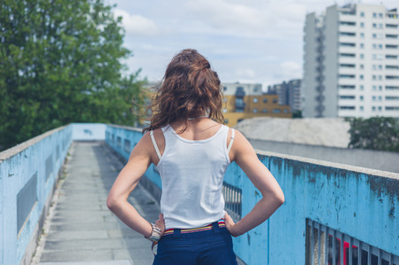 Footbridge: A stylish young woman is standing on a footbridge Stock Photo