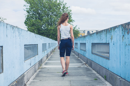 foot bridge: A young woman is walking on a foot bridge  on a sunny day Stock Photo