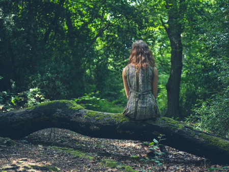 clearing: A young woman is sitting on a log in a clearing in the forest