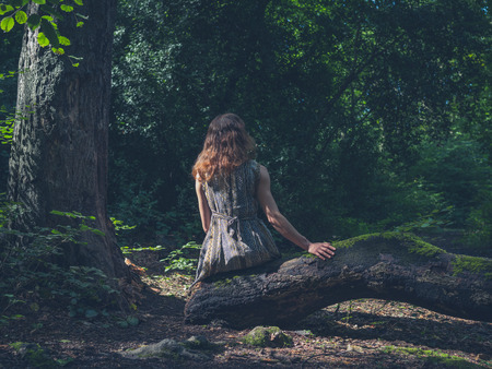 A young woman is sitting on a log in a clearing in the forest
