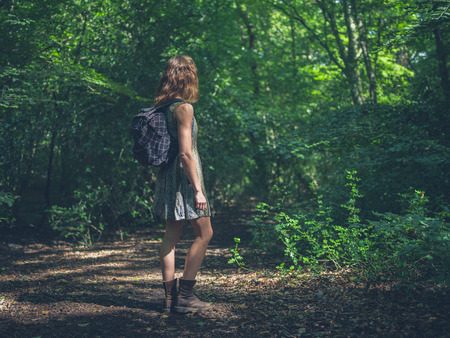 clearing: A young woman wearing a backpack is standing in a clearing in the forest